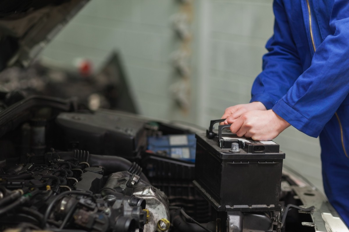 mechanic placing a car battery into a vehicle
